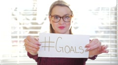 Female With Glasses Holding Up A Piece Of Paper That Reads Hashtag Goals Stock Footage