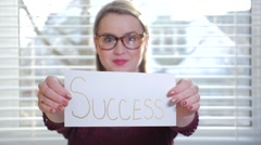 A Young Female With Glasses Holding Up A Piece Of Paper That Reads Success Stock Footage
