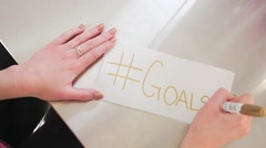 Female Hands Writing Hashtag Goals On A White Piece Of Paper Stock Footage