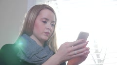 A Young Blonde Female Sitting Inside As She Types On Her Smart Phone Stock Footage