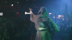 Back side of vocalist in mantle on stage in crowded nightclub. Spotlights - stock footage