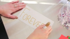 Female Hands Writing Forever On A White Piece Of Paper - stock footage