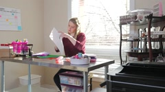 Revealing A Young Blonde Female Cutting Paper With Scissors In Her Craft Room - stock footage