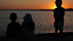 Kids are watching the sunset over the sea Stock Footage