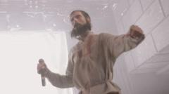 Bearded vocalist in mantle, man in folk shirt dancing on stage in nightclub - stock footage