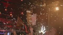 People dance in nightclub. Spotlight. Confetti. Man raise balalaika. Live - stock footage