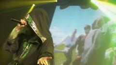 Bearded vocalist in black mantle perform on stage in nightclub. Green spotlights - stock footage