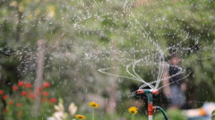 Watering of the lawn in the garden with the man on the background Stock Footage