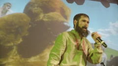 Bearded vocalist in mantle, man in folk shirt perform on stage in nightclub - stock footage