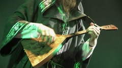 Bearded vocalist in mantle play balalaika on stage in nightclub. Green - stock footage