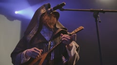 Vocalist in mantle, man in folk clothing with axe on stage in nightclub. Blue - stock footage