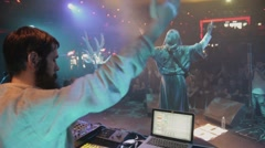 Vocalist in mantle, DJ in folk clothing wave hands on stage in nightclub. Blue - stock footage