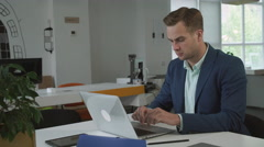 Businessman working with laptop in the office woman assistant  bring for him a Stock Footage