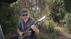 Bearded aged man in sunglasses, cap play guitar in green park. Traveling Stock Footage