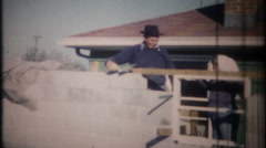 3279 bricklayer & granddaughter at work on his house - vintage film home movie Stock Footage