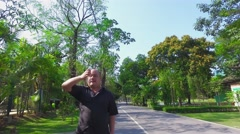 Fat Asian Thai man throwing litter on the sideway in front of sign Stock Footage
