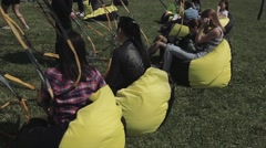 People sit on beanbags among black and yellow waving tapes on summer festival Stock Footage