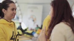 Young girl yellow hoody speak with another girl on summer festival. Sunny day Stock Footage