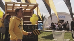 Man in yellow hoody play tennis on summer festival. Waving flags. People Stock Footage