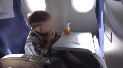 Happy child eating in airplane, kid singing and dancing, tasty food, good flight Stock Footage