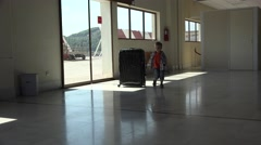 Funny little child carrying a big luggage in airport, going to a new life Stock Footage