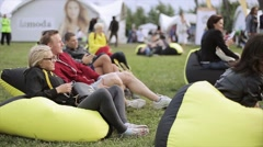 People relaxing on beanbags on summer festival. Girl smile, applaud - stock footage