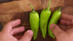 Hand throws and collects big fat green chillies on a wooden cutting board Stock Footage