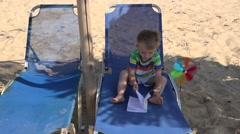 Little boy study book on sunbed near a pinwheel on the beach Stock Footage