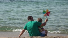Father and son sitting on seashore playing with colored pinwheel, good relation Stock Footage