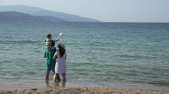 Happy family on beach, piggyback kid with pinwheel in the breeze, summer holiday Stock Footage