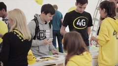 Young people at stand with booklets, girls in yellow hoody on summer festival - stock footage