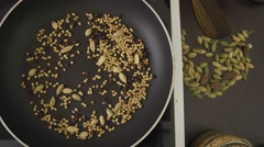 Cook adds spices and stirs in a pan Stock Footage