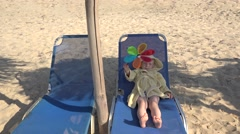 Child laying on sunbed and playing with colored hand mill - stock footage
