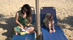 Mother reading book on sunbed, sun play with hand mill, each follow own passion - stock footage