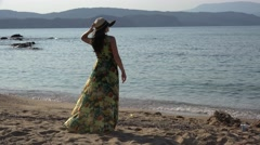 Beautiful woman standing on seashore with a hat looking to the sea, soft breeze  Stock Footage