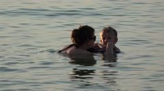 Young mother and smiling child swimming in the sea, warm sunset light Stock Footage