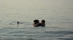 Happy child and mother swimming together, soft waves and warm sun rays caress  Stock Footage