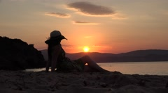 Beautiful woman sitting on seashore and admire colored sunset over sea - stock footage