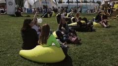 People relaxing on beaanbags on summer festival. Black and yellow waving tapes Stock Footage
