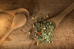 Spoon with dried oregano and thyme, basil and vegetables - stock photo
