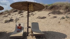 Single blonde hair child laying on sunbed drinking under umbrella, wild island Stock Footage