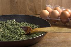 Stewed nettles with cream sauce and garlic - stock photo