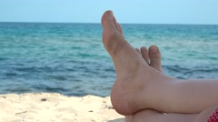 Woman barefoot relaxing on the sand, blue sea waving, closeup  Stock Footage