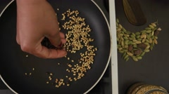 Cook throws various dry spices in a heated pan for cooking Stock Footage