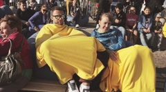 People sitting on beanbags with yellow blankets on summer festival. Audience - stock footage