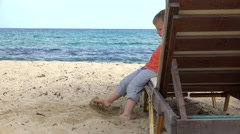 Child playing barefoot with beach sand, childhood game Stock Footage