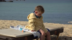 Adorable blond child with bath robe resting, snorkel equipment  Stock Footage