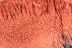 Textile background terracotta color with fringe close up - stock photo