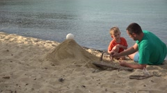 Young father and little son building a sandcastle, beautiful sunset light Stock Footage
