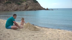 Father and son building a sandcastle Stock Footage